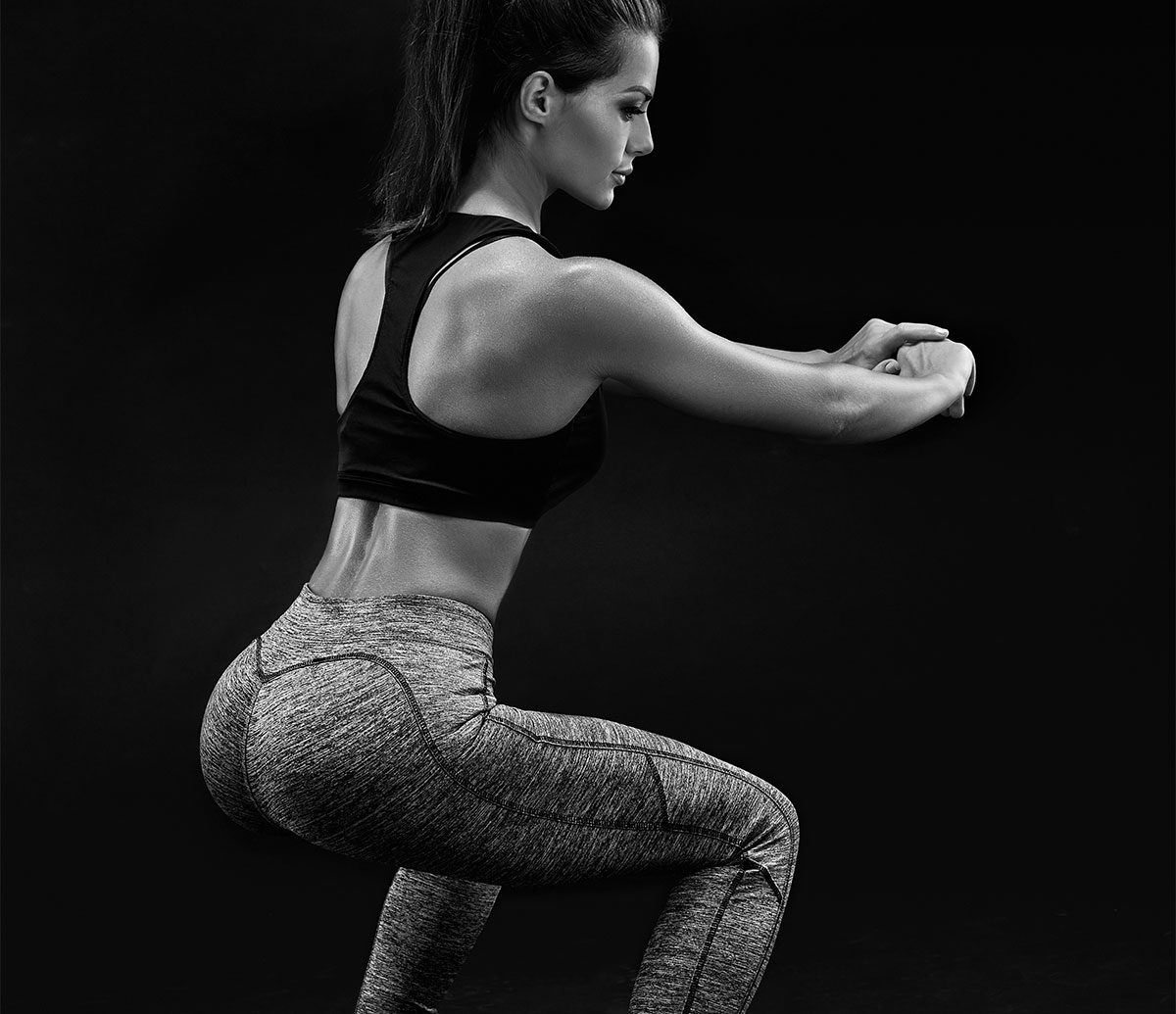 An athlete performing squats, benefitting from Powher suppliments